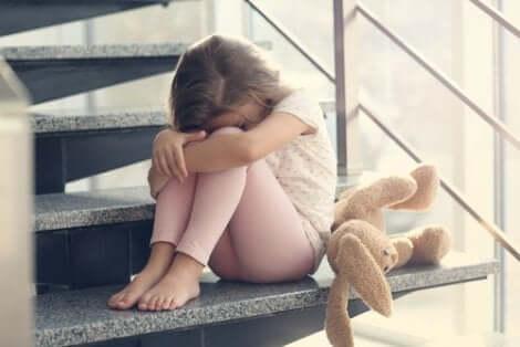 Spiegare la morte ai bambini: bambina triste con peluche.