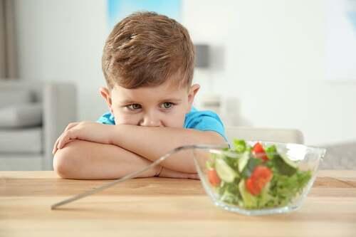 Bambino che rifiuta di mangiare l'insalata.