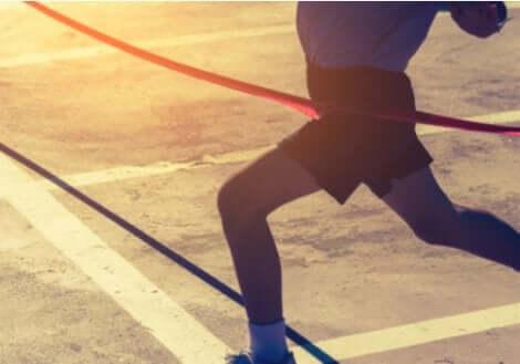 Maratona: corridore che taglia il traguardo.