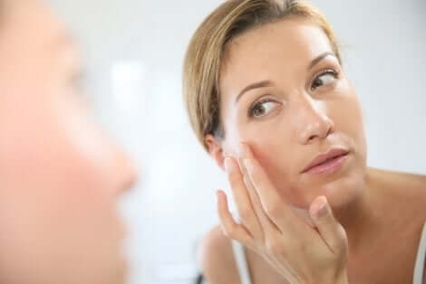 Donna che si applica una crema sul viso per contrastare il fotoinvecchiamento.