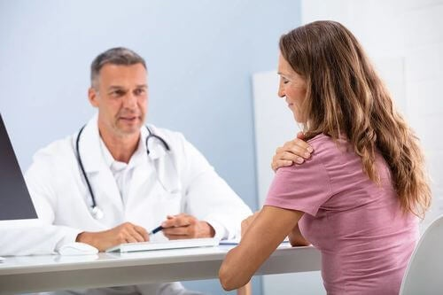 Donna con capsulite adesiva o spalla congelata dal medico.