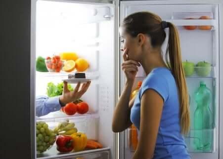 Donna guarda dentro al frigorifero.