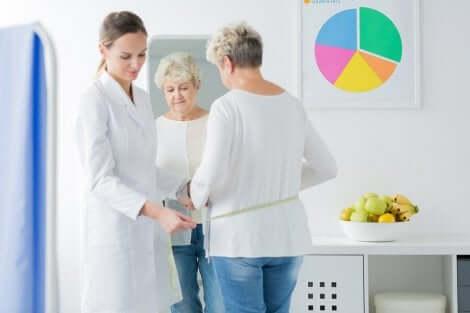 Cambiamenti del corpo durante la menopausa: medico che misura la vita di una donna.