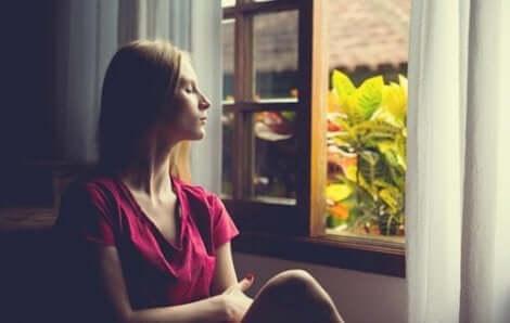 Donna con occhi chiusi seduta alla finestra.