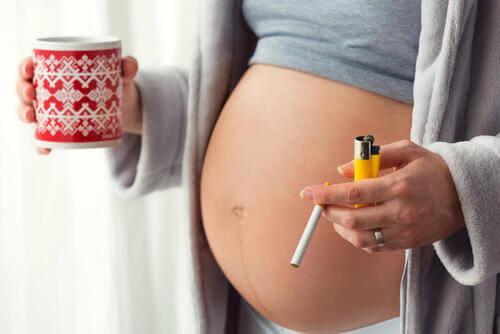 Donna con il pancione con una sigaretta in mano.