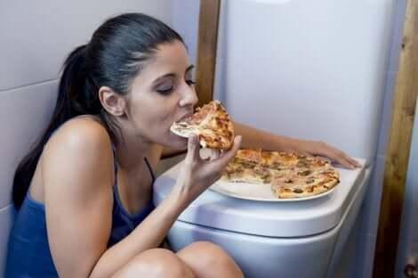 Ragazza mangia la pizza appoggiata sul water.
