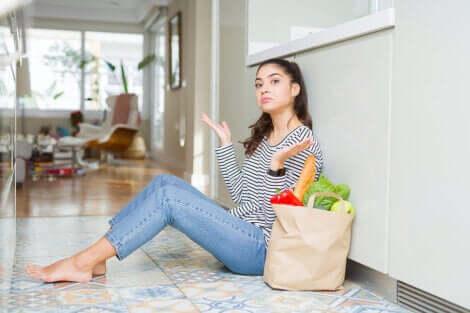 Ragazza seduta per terra con la borsa della spesa.