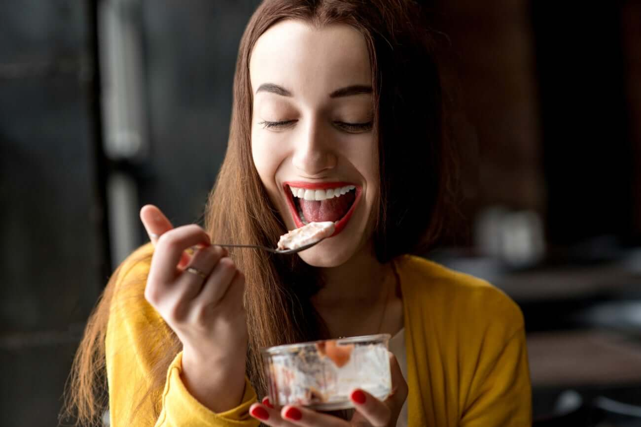 Ragazza sorridente mangia gelato.