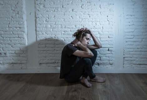 Ragazzo depresso seduto in una stanza senza luce.