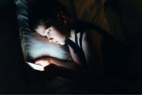Social network e bambino che usa un tablet a letto.