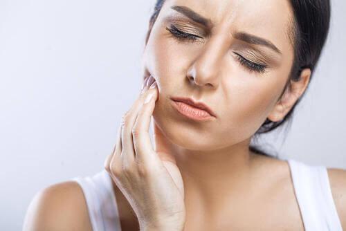 Donna che prova dolore al dente.