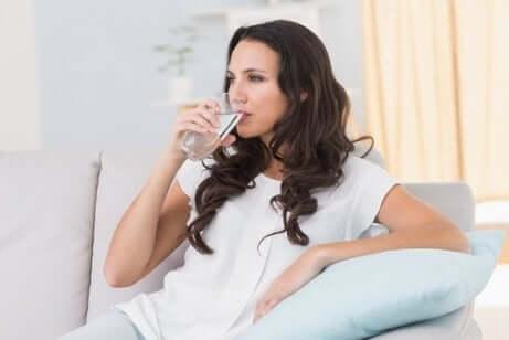 Ragazza beve un bicchiere d'acqua.