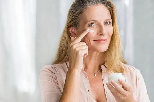 Donna che usa una crema antietà per la cura della pelle.