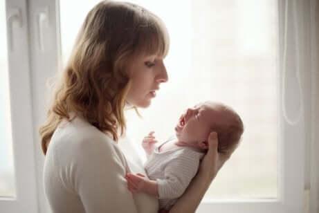 Madre con neonato che piange.