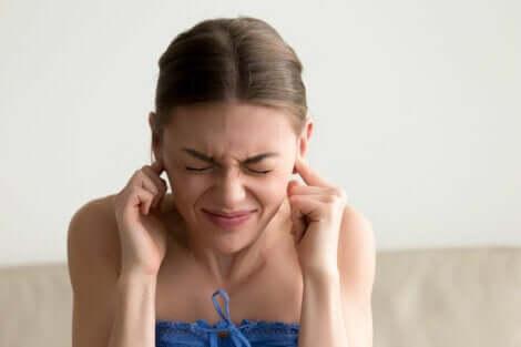Ragazza si tappa le orecchie per il tinnito.