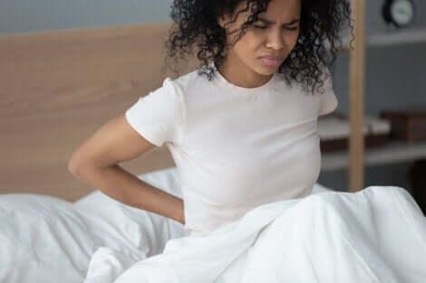 Ragazza sul letto con mal di schiena.
