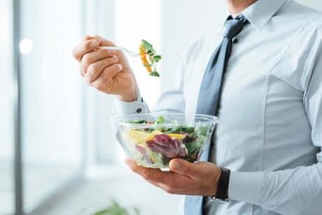 Uomo che mangia un'insalata.