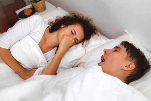 Coppia a letto che respira con la bocca aperta.