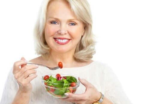 Donna che mangia un'insalata.