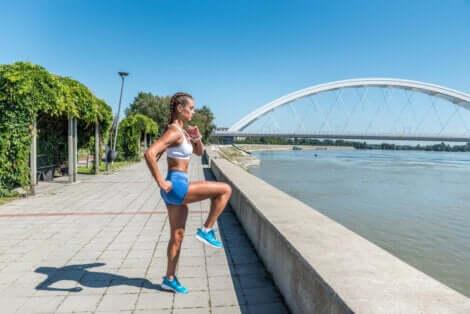 Donna esegue esercizi di riscaldamento sul lungomare.