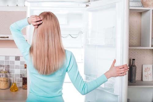 Donna che apre il frigorifero.