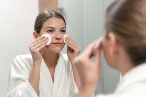 Donna applica prodotti cosmetici allo specchio.