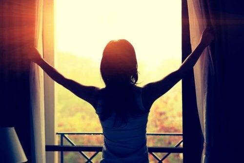 Donna che fa entrare la luce del sole.