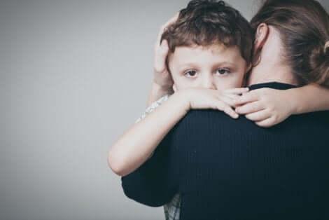 Bambino abbracciato dalla mamma.