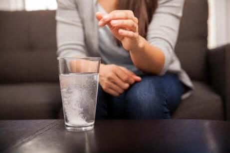 Ragazza scioglie aspirina nell'acqua.