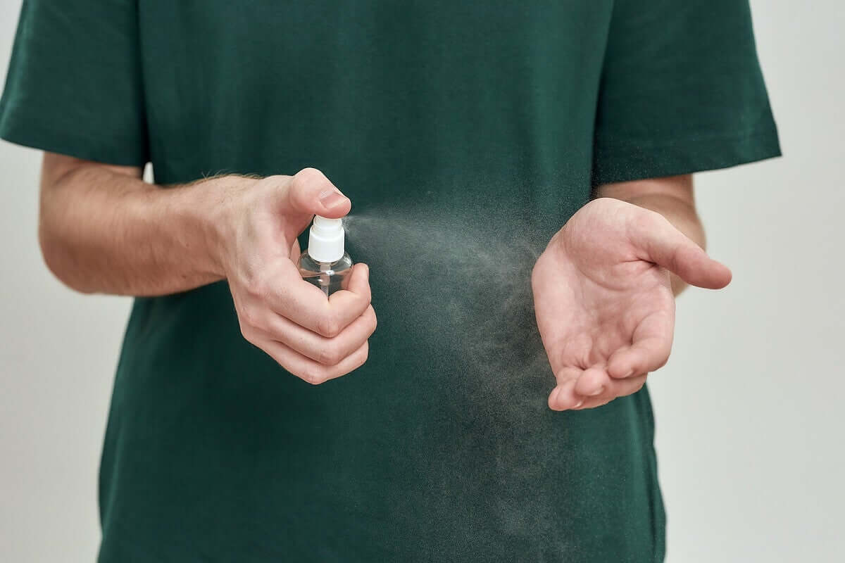 Uomo usa spray sulle mani.