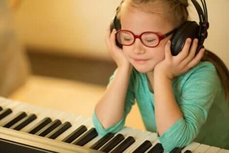 Bambina al piano con le cuffie.