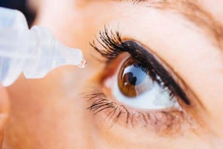 Donna usa collirio per gli occhi secchi.