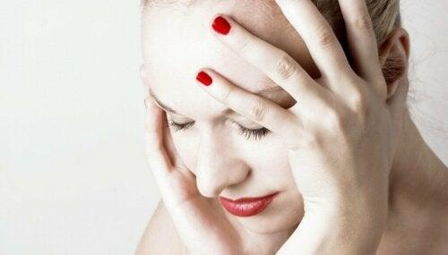 Donna con dolore alla testa.