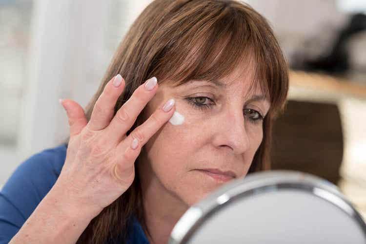Donna si spalma crema per il viso.