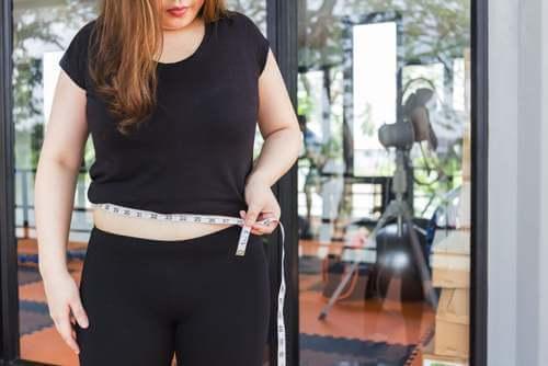 Donna che si misura il ventre.