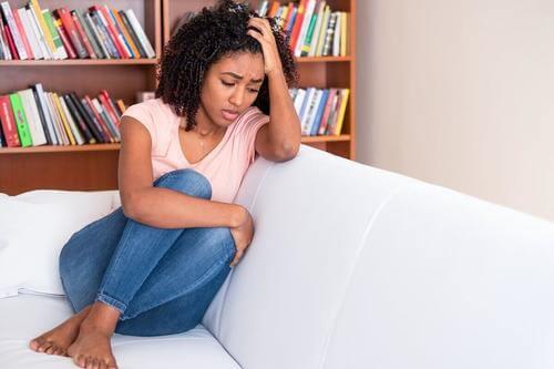 Donna triste sul divano.