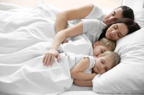 Gemelli dormono nel lettone con mamma e papà.