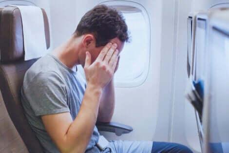 Uomo che soffre di stress e malessere in aereo.
