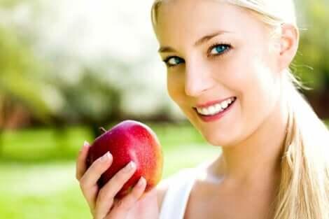 Ragazza sorridente mangia una mela.