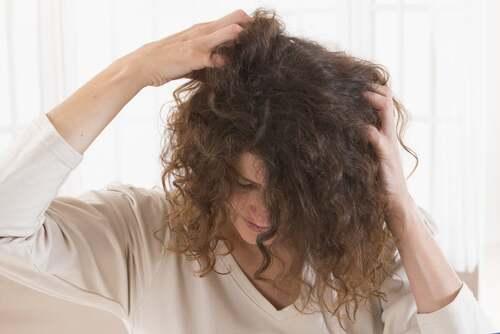 Donna che si massaggia il cuoio capelluto.