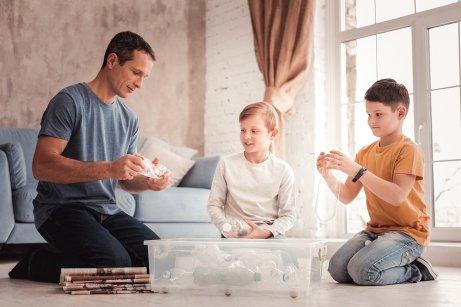 Padre e figli separano la plastica dal cartone.