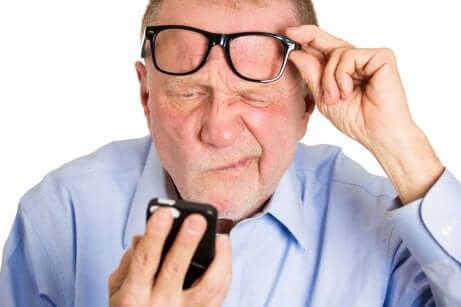 Uomo anziano solleva gli occhiali per leggere sul cellulare.
