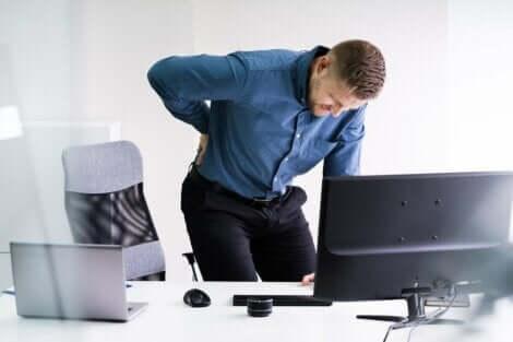 Uomo in ufficio con mal di schiena.