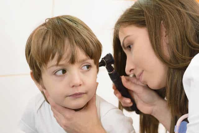 Bambino con otorino visita orecchio.