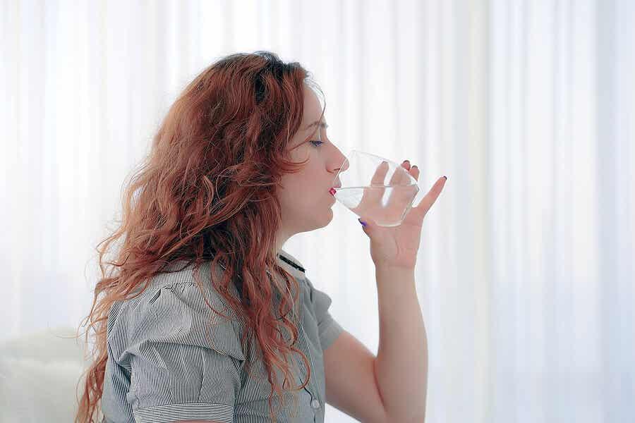 Donna beve un bicchiere d'acqua.