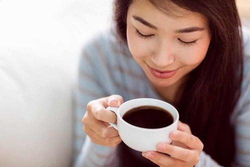 Donna che sorride davanti a un caffe.