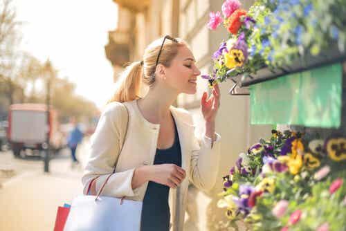 Donna che annusa un fiore.