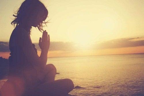 Donna che medita al tramonto.