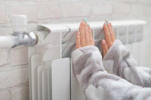Donna con le mani sul termosifone.
