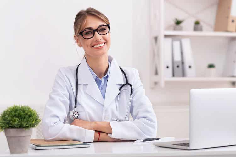 Dottoressa sorridente che parla di ferro e calcio nella donna.